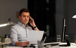Бизнесмен вызывая на офисе sartphone вечером стоковая фотография