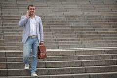 Бизнесмен вызывая телефон на городской предпосылке Директор зрелого дела Финансовая концепция дела скопируйте космос Стоковые Фотографии RF