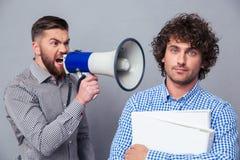 Бизнесмен выкрикивая через мегафон к другому человеку стоковая фотография