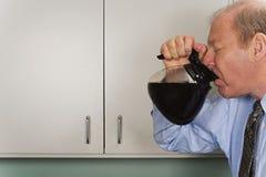 Бизнесмен выпивая из бака кофе Стоковое Фото