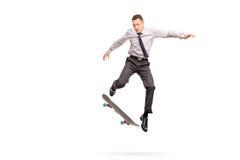 Бизнесмен выполняя фокус с скейтбордом стоковые изображения
