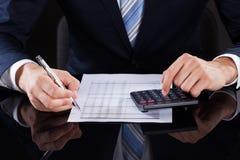 Бизнесмен высчитывая финансовые расходы на столе Стоковые Изображения