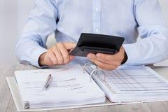 Бизнесмен высчитывая финансовые расходы Стоковые Фото