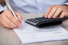 Бизнесмен высчитывая финансовые расходы Стоковое Изображение