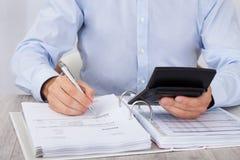 Бизнесмен высчитывая финансовые расходы Стоковое фото RF
