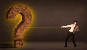 Бизнесмен вытягивая большой твердый камень вопросительного знака Стоковое фото RF