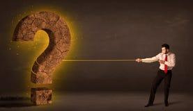 Бизнесмен вытягивая большой твердый камень вопросительного знака Стоковые Фотографии RF