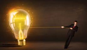 Бизнесмен вытягивая большую яркую накаляя электрическую лампочку Стоковое фото RF