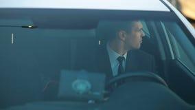 Бизнесмен в автомобиле, смотрящ вокруг, наблюдая что случается видеоматериал