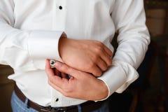 Бизнесмен в белой рубашке выправляет тумаки, стоя на окне в естественном свете Человек застегивает запонку для манжет на sle тума стоковое фото rf