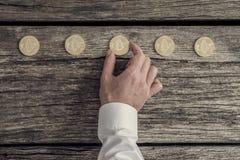 Бизнесмен в белой рубашке устанавливая 5 золотых bitcoins в ряд Стоковая Фотография RF