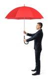 Бизнесмен в взгляде со стороны держит открытый красный зонтик в обеих руках перед им Стоковая Фотография RF