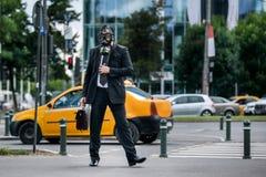 Бизнесмен в городе нося маску противогаза на его стороне стоковая фотография