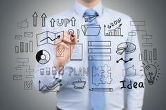Бизнесмен в голубой рубашке рисует startup эскиз идеи на a Стоковые Фото