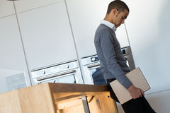 Бизнесмен в его кухне с цифровой таблеткой Стоковые Изображения