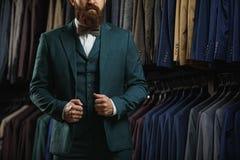 Бизнесмен в классическом жилете против строки костюмов в магазине Стоковая Фотография
