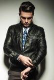 Бизнесмен в кожаной куртке, смотря вниз пока фиксирующ его sl Стоковые Изображения RF