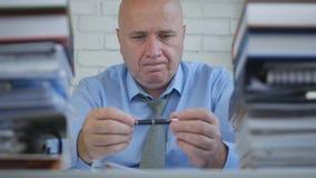 Бизнесмен в комнате офиса думая и играя с ручкой в руках стоковое изображение rf