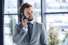 Бизнесмен в костюме говоря на smartphone в офисе Стоковое фото RF