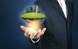 Бизнесмен в костюме держа зеленый остров с городом skycraper внутри стоковое изображение