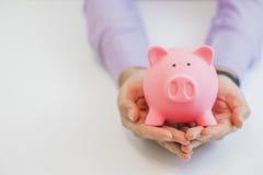 Бизнесмен в костюме держа розовую копилку с обеими руками Стоковое Фото
