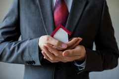 Бизнесмен в костюме используя руки покрывая и защищая дом Стоковые Фото