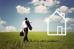 Бизнесмен в костюме идя к дому к просторному зеленому цвету f Стоковое Фото