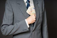 Бизнесмен в костюме кладя банкноты в его нагрудный карман куртки Бизнесмен держит наличные деньги, стог денег 50 евро Pers Стоковая Фотография RF