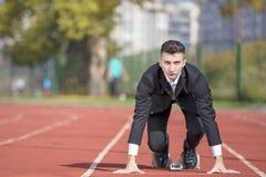 Бизнесмен в костюме начиная и подготавливая побежать на следе проведения конкуренции идущем стоковое фото