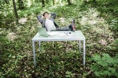 Бизнесмен в костюме ослабляет на его работая столе офиса в зеленом парке с руками накладными расходами и ногами на таблице конец  Стоковые Изображения