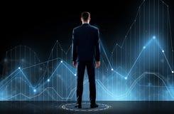 Бизнесмен в костюме от задней части с виртуальной диаграммой Стоковое фото RF