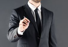 Бизнесмен в костюме поя что-то, изолированный на сером цвете стоковое фото rf