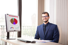 Бизнесмен в костюме работая на его компьютере рядом с стеклянным ветром Стоковая Фотография