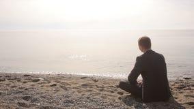 Бизнесмен в костюме сидя на камнях пляжа бросая в воде и показывать приглашает для того чтобы соединить акции видеоматериалы