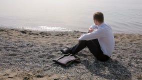 Бизнесмен в костюме сидя на пляже бросает камни в воду сток-видео