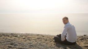 Бизнесмен в костюме сидя на пляже и показывать приглашать, который нужно соединить акции видеоматериалы