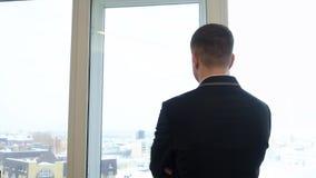 Бизнесмен в костюме смотря на городском пейзаже из окна в офисе сток-видео