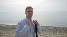Бизнесмен в костюме стоя на пляже, принимает его куртку, связь и unbuttons рубашка акции видеоматериалы