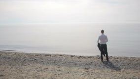 Бизнесмен в костюме стоя на пляже, принимает его куртку, связь и unbuttons рубашка видеоматериал