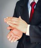 Бизнесмен в костюме с красным жестом показа связи аплодирует стоковое изображение