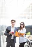 Бизнесмен в костюме с таблеткой и кофе в руках разговаривая с бизнес-леди над тетрадью о строгать владение домашнего ключа принци Стоковые Изображения RF