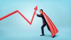 Бизнесмен в красной пропуская накидке пробуя согнуть красную стрелку статистики вверх на голубой предпосылке Стоковое Фото