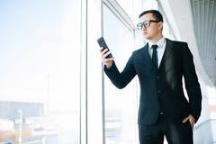 Бизнесмен в мобильном телефоне пользы костюма для того чтобы проверить электронную почту или написать сообщение в комнате офиса Стоковые Изображения