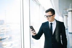 Бизнесмен в мобильном телефоне пользы костюма для того чтобы проверить электронную почту или написать сообщение в комнате офиса Стоковое Изображение
