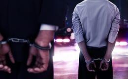 Бизнесмен 2 в наручниках на ноче стоковая фотография