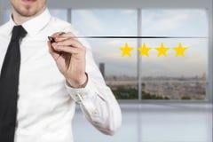 Бизнесмен в офисе нажимая звезды оценки кнопки 4 золотые Стоковые Фото