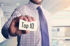 бизнесмен в офисе показывая карточку с текстом: 10 лучших Стоковое Фото