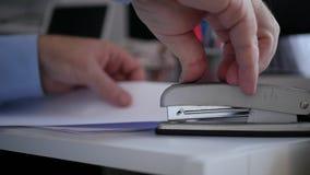 Бизнесмен в офисе помещая документы в архив использует сшиватель для бумаг сток-видео