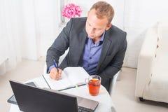 Бизнесмен в офисе сидя на таблице с компьтер-книжкой пишет концентрацию Стоковое Фото