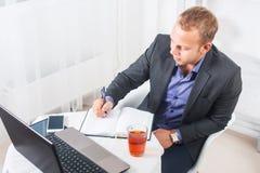 Бизнесмен в офисе сидя на таблице с компьтер-книжкой пишет концентрацию Стоковая Фотография
